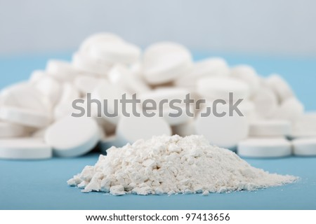 forefront of crushed pills on a blurred background of whole tablets - stock photo