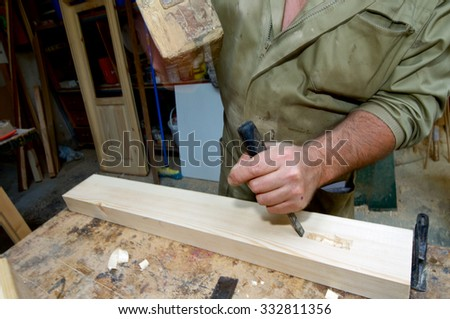 Forefront of the hands of a carpenter working. - stock photo
