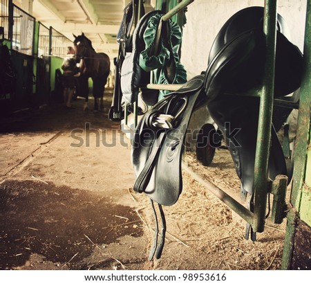 forefront of the saddle, harness, in the background a woman cleans horse - stock photo