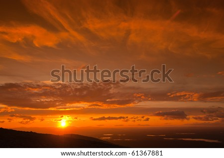 Foreground has a silhouette of mountain. In the background many small lakes and orange sunset. - stock photo