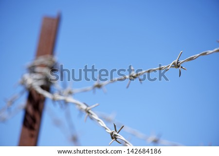 foreground of a barbed wire fence - stock photo