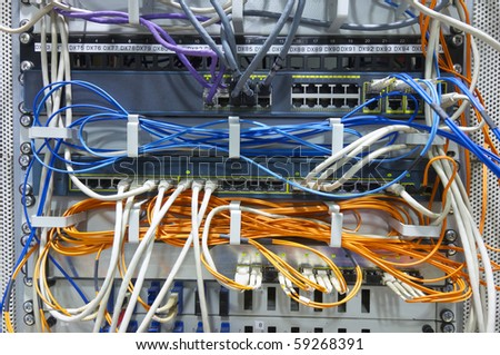 foreground of a network hub and patch cables - stock photo