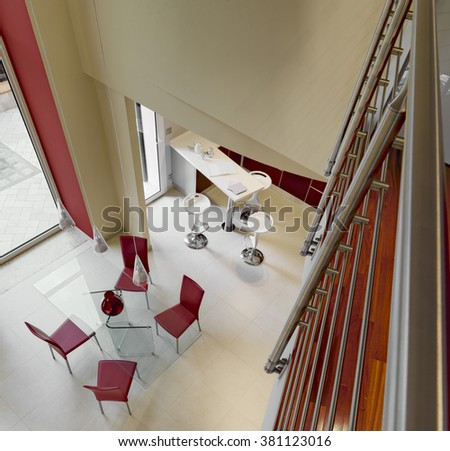 foreground of glass dining table , red leather chairs and the kitchen view from above  - stock photo