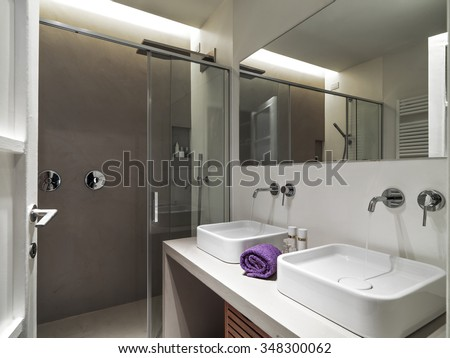 foreground of two washbasin in the modern bathroom overlooking on the shower cubicle - stock photo