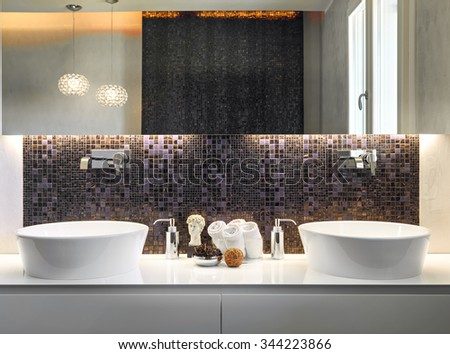 foreground of two washbasin with mosaic tiles and large mirror in the modern bathroom - stock photo