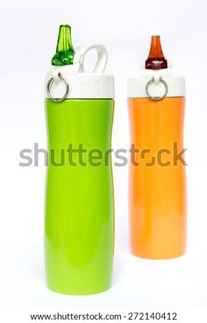 Foreground on green and orange thermos travel tumbler - stock photo