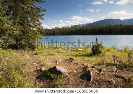 Foreground shoreline of Edith Lake located in Jasper National Park with pine trees and mountain range in the background - stock photo