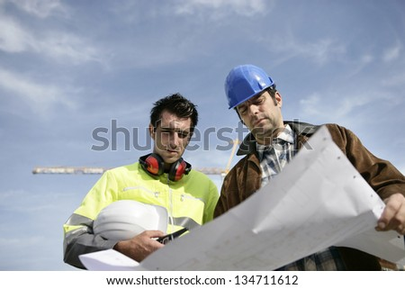 Foreman and colleague at construction site - stock photo