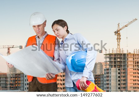Foreman and engineer with blueprints at construction site - stock photo