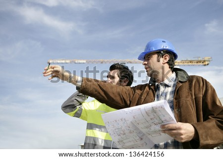 Foreman and worker on a site - stock photo