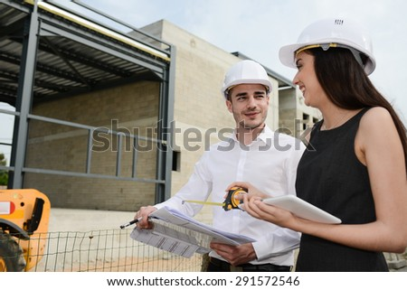 foreman architect man and woman supervising building construction site with blueprint