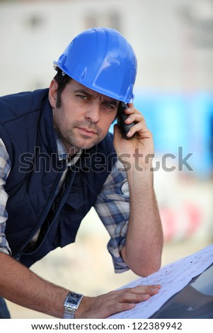 Foreman  checking plans whilst on the phone - stock photo