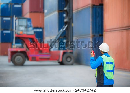 foreman control forklift handling the container box load to big truck - stock photo