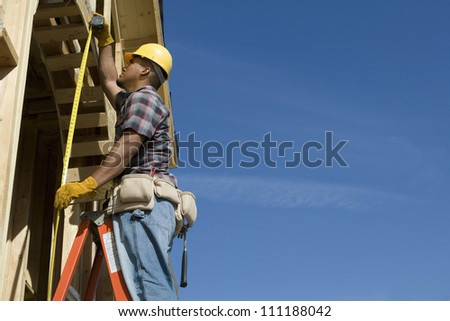 Foreman examining with measure tape at construction site - stock photo
