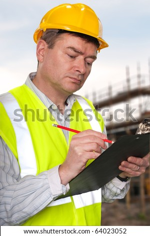 Foreman on construction site checks details on a clipboard.