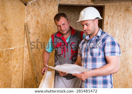 Foreman Wearing White Hard Hat and Worker Looking at Building Plans Together Inside Unfinished Frame of New Home - stock photo