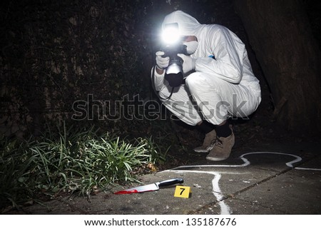 Forensics researcher photographing a blood stained knife at a murder scene - stock photo