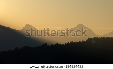 Forest and mountain silhouettes at sunrise - stock photo