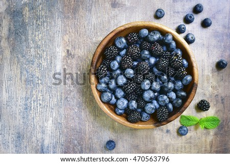 Forest berries (blueberry,bramble) in a wooden bowl.Top view.Space for text.