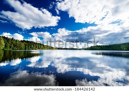 Forest lakes mirroring clouds - stock photo