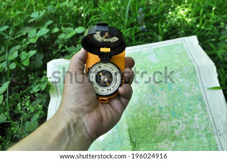 Forest, may, walk in the woods. Compass in hand, against the background of the map. - stock photo