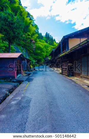 Forest on one side, traditional wooden home on other on this stretch of Nakasendo trail between Magome-Tsumago in the post town of Tsumago, Japan on a blue sky day