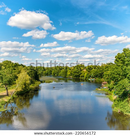 Forest on the river with blue sky and landscape of clouds - stock photo