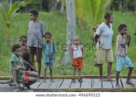 FOREST SMALL VILLAGE, IRIAN JAYA, NEW GUINEA, INDONESIA - MAY 22, 2016: Group of people of asmat in small deaf traditional village in jungle of  New Guinea Island. May 22, 2016