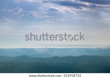 Forested mountains and sky. A slight mist-shrouded mountains and trees. Clear sky