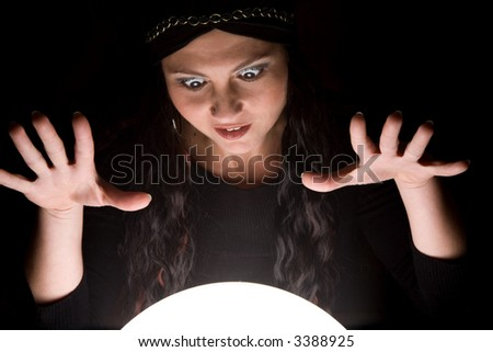 Foretunneller looking into her crystal ball with a look of madness on her face - stock photo