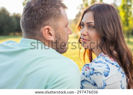 Forever together. Young attractive man and beautiful woman are looking at each other with love. They are sitting in park - stock photo