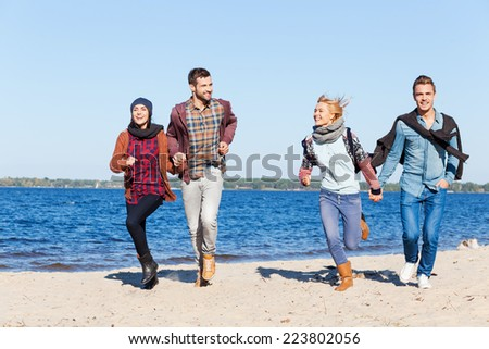 Forever young and free. Full length of two beautiful young couples running by the beach together and smiling - stock photo