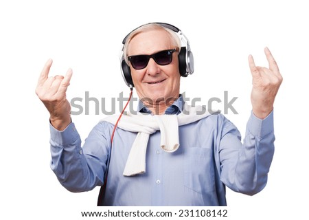 Forever young. Cheerful senior man in headphones listening to music and showing hand sign while standing against white background  - stock photo