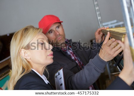 forewoman and worker inspecting shelves in workshop