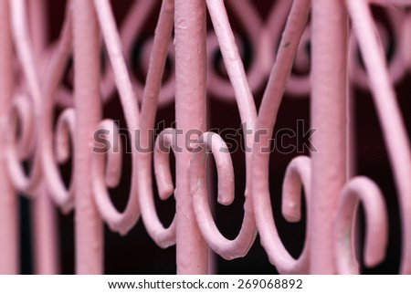 Forge Detail. Part of a wrought iron fence. Design pink iron gate details. - stock photo