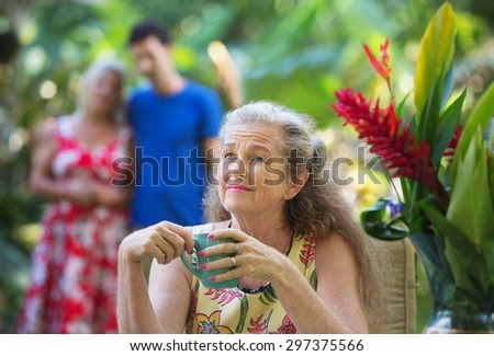 Forgetful older mother with cup near couple - stock photo