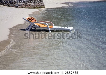 Forgotten beach lounger with towel ends up in the water as the ocean tide comes in. - stock photo