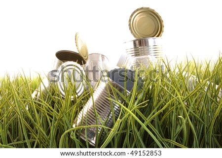 Forgotten empty cans and bottles laying in the grass - stock photo