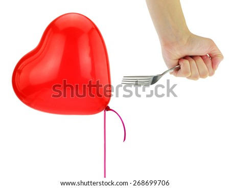 Fork about to pop a heart balloon isolated on white - stock photo