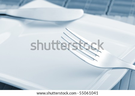 Fork and a knife laying on a plate. A photo close up. Blue tone