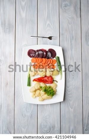 fork and cut vegetables on white table - stock photo