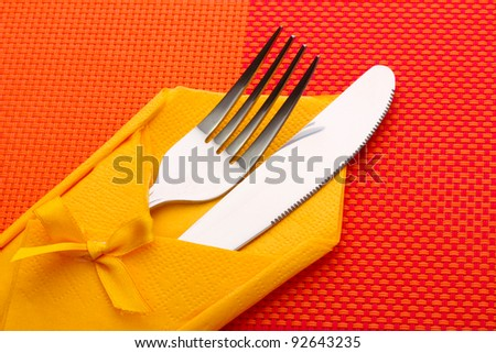 Fork and knife in a yellow cloth with a bow on a red tablecloth - stock photo