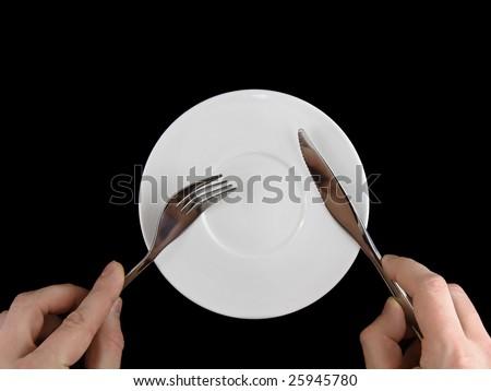 Fork and  knife  in  hands on black background. - stock photo