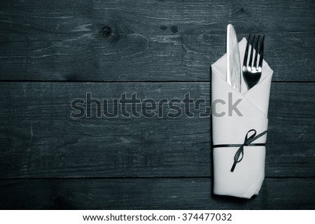 Fork and knife in napkin on wooden background. Toned. - stock photo