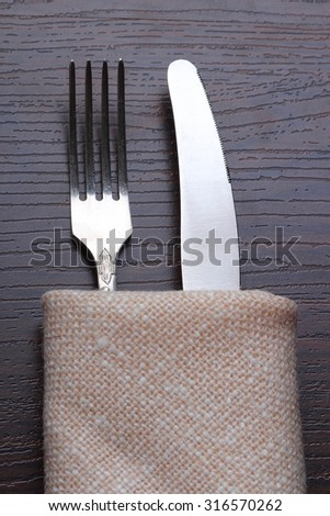 Fork and knife in napkin on wooden table. Closeup - stock photo