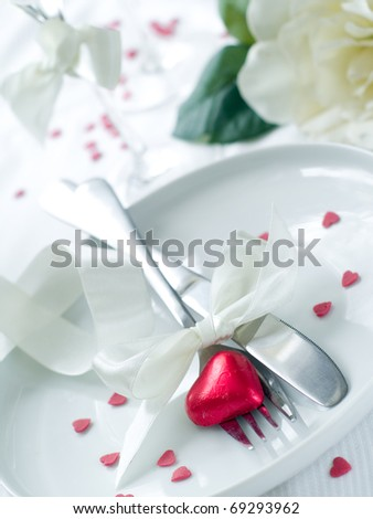 Fork and knife laying on plate with ribbon and heart - stock photo