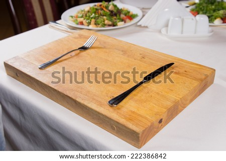 Fork and Knife on Rectangular Wooden Chopping Board Placed on White Table. - stock photo