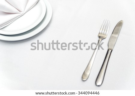 Fork and knife on the white tablecloth. Near the edge of plates