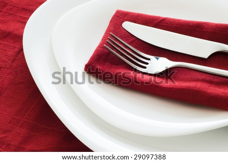 fork and knife on white plates and dark red napkin - stock photo