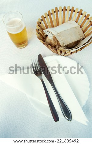 Fork and knife over white plate and napkin with beer and bread basket - stock photo